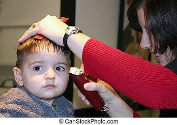 First Hair Cut - Small boy getting his first hair cut. Focus...