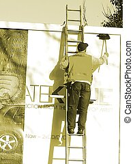 Billboard Worker - Man putting up a new billboard poster