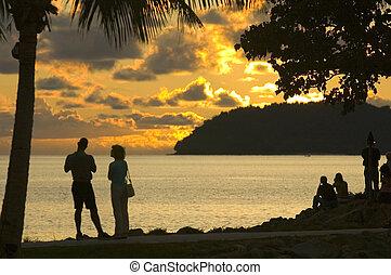 sunset - couples watching sunset at tanjung aru, sabah,...