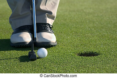 Putting - Golfer about to put ball in hole