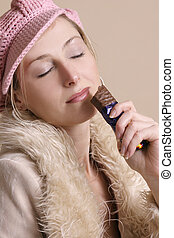 Winter munchies - Girl enjoys chocolate bar