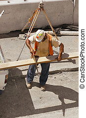 Builder with a hand saw - Builder saws a plank of wood....