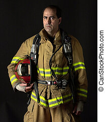 Fire Fighter - Fire fighter wearing bunker gear on dark...