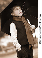 Standing in the rain - Sepia toned young boy in the rain...