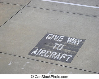 Give Way Sign - Give Way to Aircraft stenciled on tarmac.