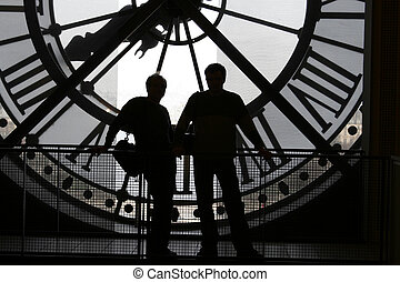2 silhouettes against the clock at the Orsay Museum (Musée...