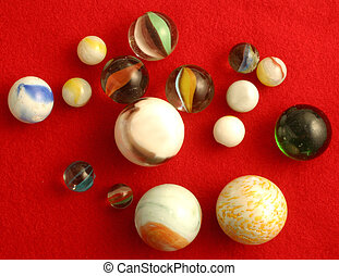 marbles on red - Different sized marbles.