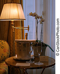 Hotel room with champagne and flowers by the window