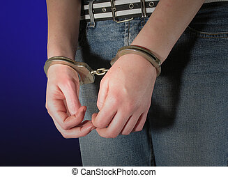 Handcuff woman - Young woman\\\'s hands in handcuffs on blue...
