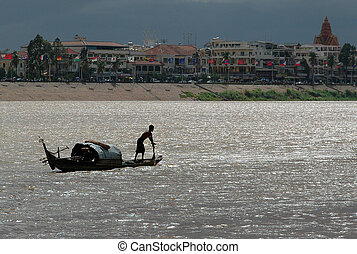 Mekong River - A boat meanders up the Mekong river in...