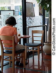 Coffee bar - A woman in a coffee bar sitting and reading a...