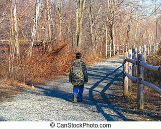 boy walking down trail