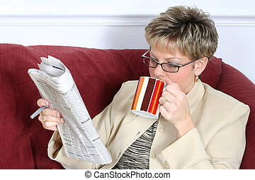 Coffee and Newspaper - Beautiful woman in business suit on...