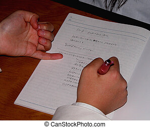 Writing - Two student hands writing notice during a...