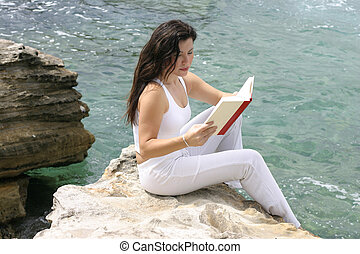 Leisure time - Woman relaxes reading a book. Focus on woman...