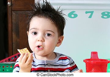 Preschool Snacktime - Two year old boy eathing crackers at...