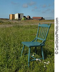 Places to sit 1 - Empty chair in a meadow with junkyard in...
