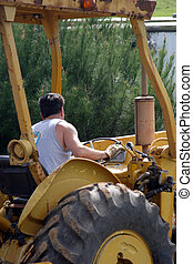 Man on Tractor - A man operating a large tractor.
