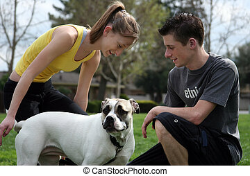 Teens with a dog - Teenagers playing with a dog in the park