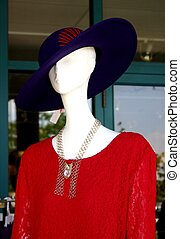 Red Dress - A mannequin wearing a red dress and purple hat...