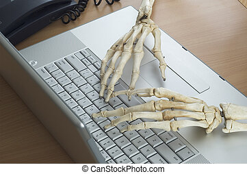 Skeleton at Work 4 - Skeleton hands type on a computer