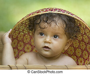 Infant in Hat - A toddler enjoying a bath in a tropical...