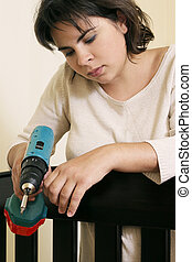 Preparing for baby - Young mother with power tool by cot