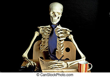 Skeleton at Desk - A skeleton sits at a desk with a...