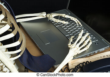 Skeleton keyboard - A skeleton types on a laptop computer