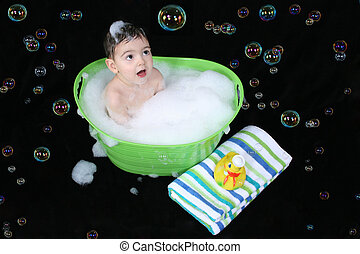 Bubble Bath - Two year old boy in a green tub of bubble...