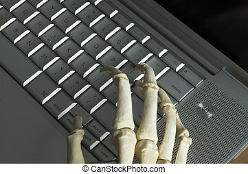 Skeleton Hands - Skeleton fingers type on a laptop computer