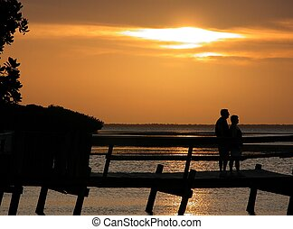 Watching A Sunset - People silhouetted against a beautiful...