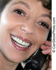 Smiling woman - Closeup of a smiling woman talking on the...