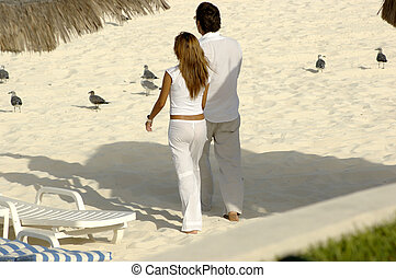 Lovers at the beach - Young couple holding hands and walking...