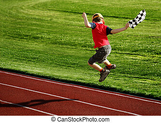 Boy on a racetrack - Boy with a checked flag jumping on a...