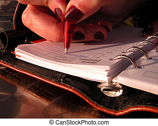 Writing the schedule - A girl hand writing the schedule in...