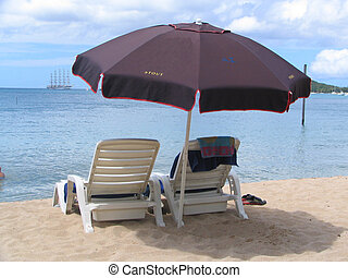 Tropical Beach - Two Deck Chairs and umbrella on a beach on...
