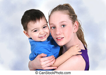 Children Hugging - Toddler boy and teen girl hugging and...
