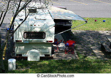 Campsite - Backside of a camper and two chairs.