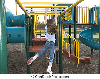 PlayGround - A young girl does the hanging walk along the...