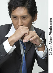 Serious - An asian businessman sits and thinks