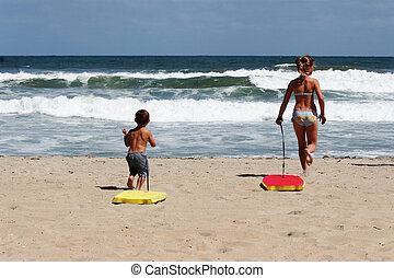 Kids on the beach - Kids with boogie boards on the beach
