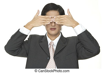 Blind - An asian businessman covers his eyes with his hands