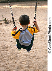 Boy Swing Park - Backside of toddler boy on a swing at the...