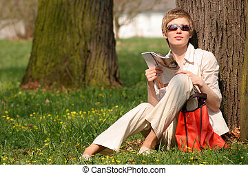 first sunbathe - smart dressed lady sitting with magazine at...