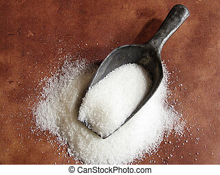 sugar scoop - scoop of granulated white sugar against brown...