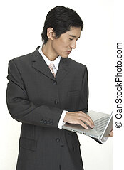 On The Move - an asian businessman keeps up to date using...