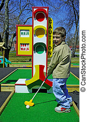 Miniature Golf - Young Boy Playing Miniature Golf