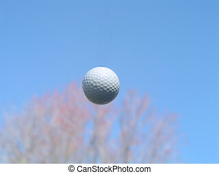 Golf ball in flight - closeup of a golf ball in the air with...