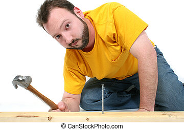 Man Hammer Nail - Man in yellow shirt and jeans hammering in...